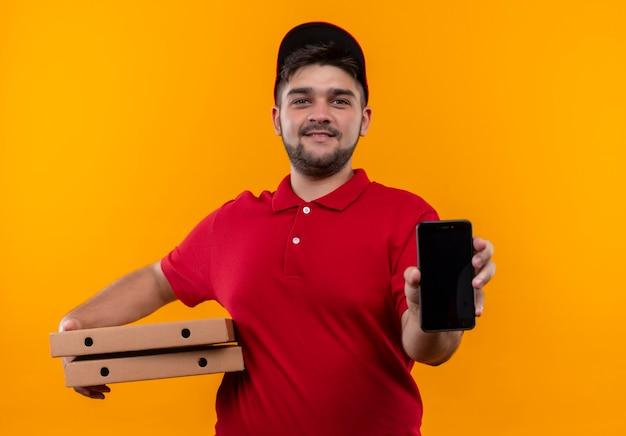Jovem entregador de uniforme vermelho e boné segurando uma pilha de caixas de pizza mostrando smartphone sorrindo amigável