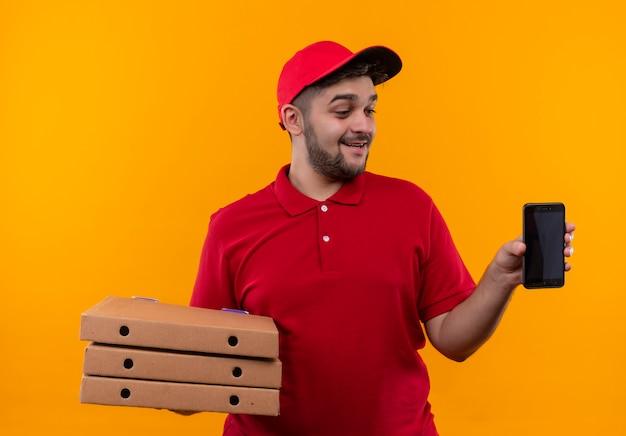 Jovem entregador de uniforme vermelho e boné segurando uma pilha de caixas de pizza mostrando um smartphone olhando para ele com um sorriso no rosto