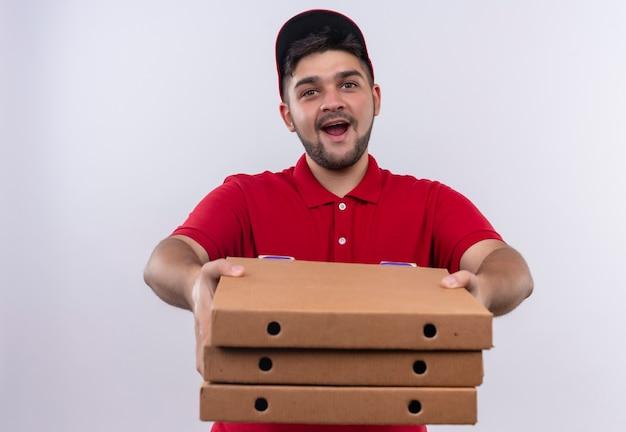 Jovem entregador de uniforme vermelho e boné segurando uma pilha de caixas de pizza, parecendo confiante e sorrindo amplamente