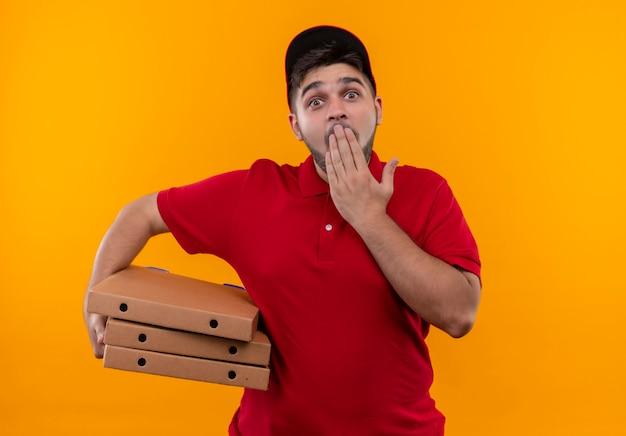 Jovem entregador de uniforme vermelho e boné segurando uma pilha de caixas de pizza surpreso e surpreso, cobrindo a boca com a mão
