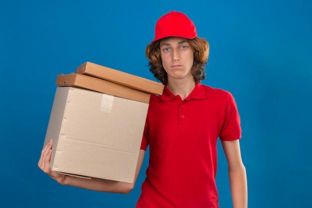 Jovem entregador de uniforme vermelho segurando caixas de papelão, olhando para a câmera, nervoso e cético em pé sobre um fundo azul isolado