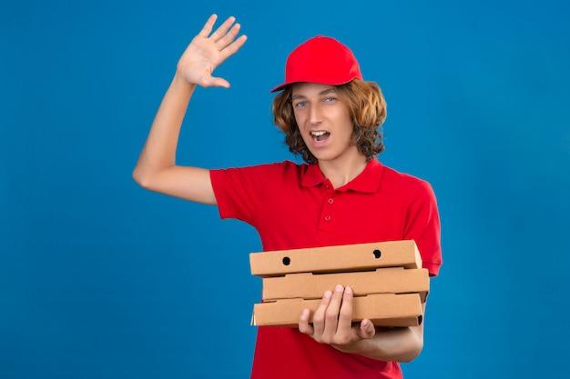 Jovem entregador de uniforme vermelho segurando caixas de pizza acenando com a mão e sorrindo alegremente sobre um fundo azul isolado