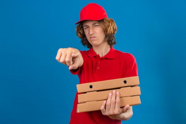 Jovem entregador de uniforme vermelho segurando caixas de pizza apontando descontente e frustrado para a câmera, zangado e furioso com você sobre um fundo azul isolado