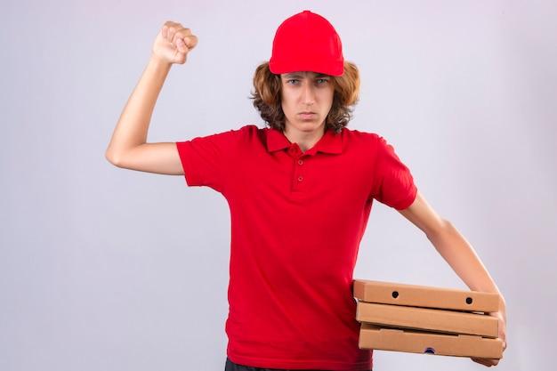 Jovem entregador de uniforme vermelho segurando caixas de pizza com raiva e com raiva levantando o punho frustrado e furioso, olhando para a câmera com raiva sobre fundo branco isolado