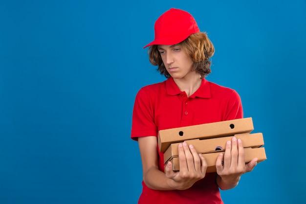 Jovem entregador de uniforme vermelho segurando caixas de pizza olhando para o lado com uma expressão triste sobre um fundo azul isolado