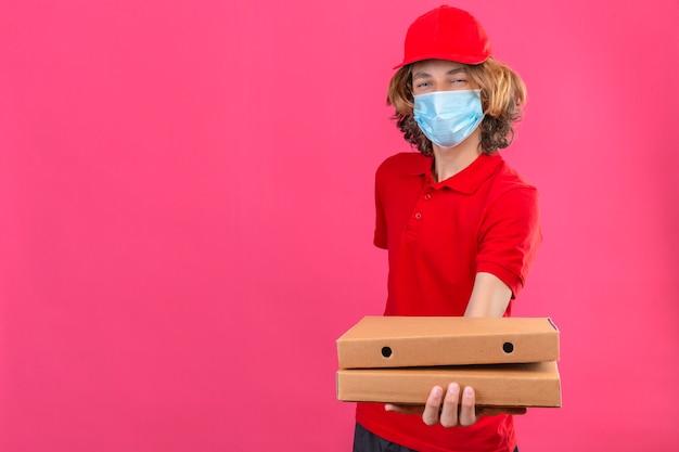 Jovem entregador de uniforme vermelho usando máscara médica esticando caixas de pizza, sorrindo amigável em pé sobre um fundo rosa isolado com espaço de cópia