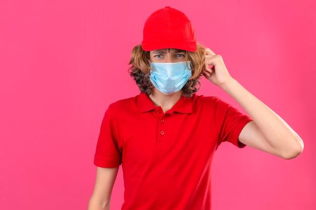 Jovem entregador de uniforme vermelho, usando máscara médica, surpreso com a mão na cabeça por engano, lembre-se do erro, esqueceu o conceito de memória ruim sobre fundo rosa isolado