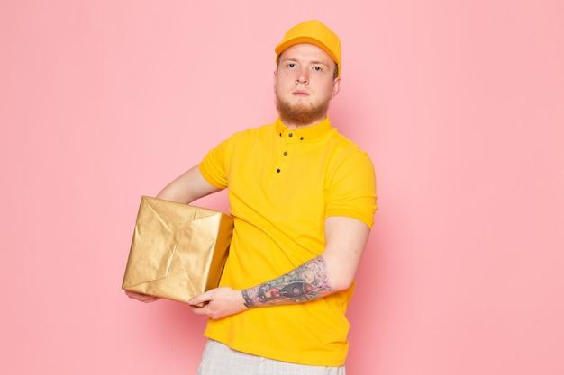 Jovem entregador em polo amarelo boné amarelo jeans branco segurando uma caixa rosa