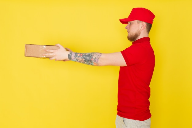 Jovem entregador em polo vermelho boné vermelho jeans branco segurando uma caixa em amarelo