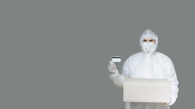 Jovem entregador em traje de proteção com luvas e máscara segurando um cartão de crédito e uma caixa de papelão em um cinza