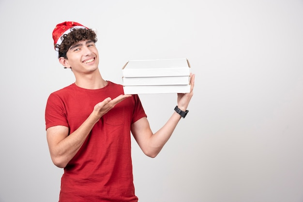 Jovem entregador exibindo caixas de pizza.