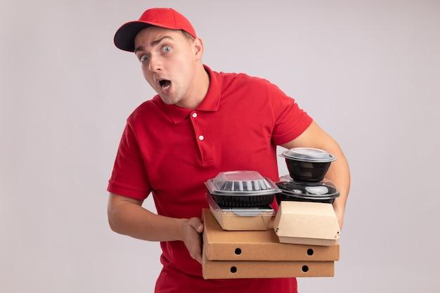 Jovem entregador impressionado usando uniforme com tampa segurando recipientes de comida em caixas de pizza isoladas na parede branca