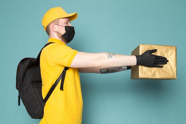 Jovem entregador no polo amarelo boné amarelo jeans branco mochila e máscara estéril preta, segurando uma caixa em azul