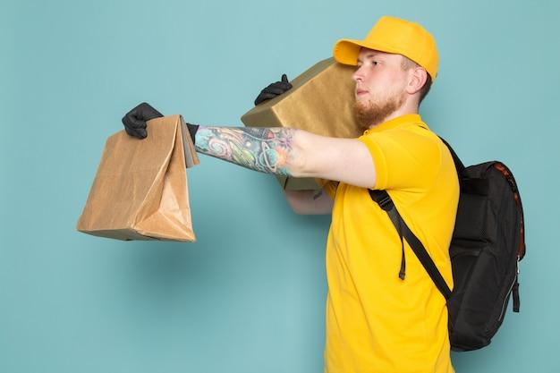 Jovem entregador no polo amarelo boné amarelo jeans branco mochila segurando uma caixa em azul