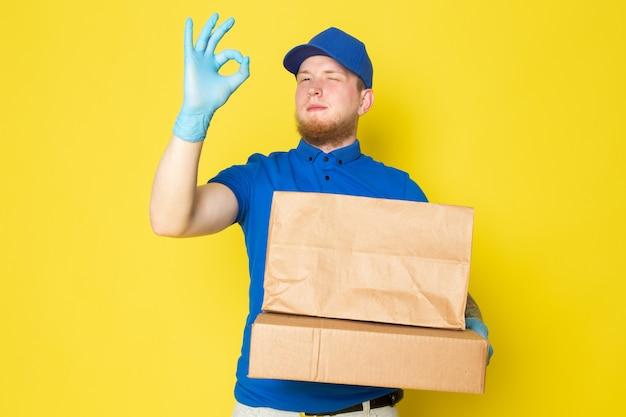 Jovem entregador no polo azul boné azul jeans branco mochila segurando caixas em amarelo