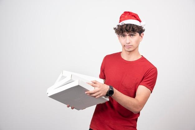 Jovem entregador posando com caixas de pizza.