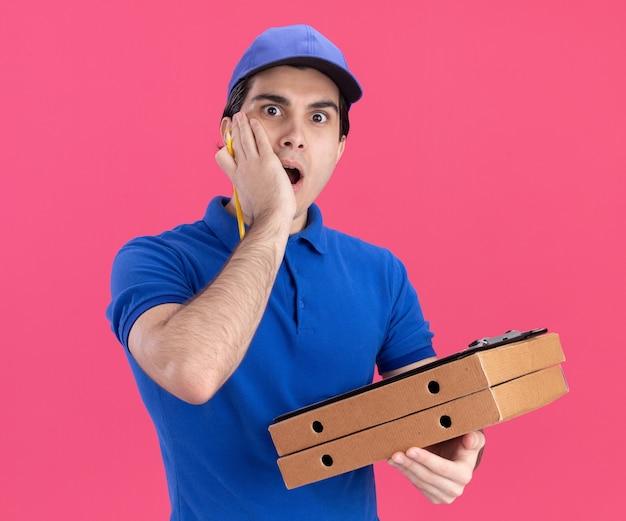 Jovem entregador preocupado com uniforme azul e boné segurando pacotes de pizza e prancheta com lápis olhando para frente mantendo a mão no rosto isolado na parede rosa