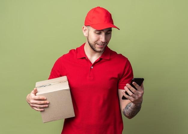 Jovem entregador satisfeito vestindo uniforme com tampa segurando uma caixa e olhando para o telefone na mão