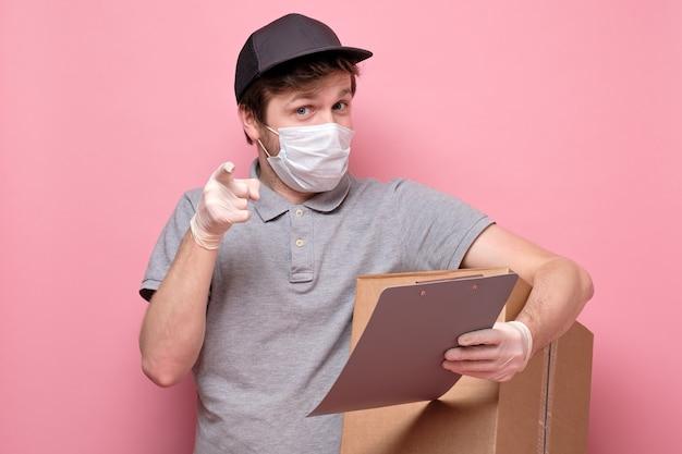 Jovem entregador segurando e carregando uma caixa de papelão