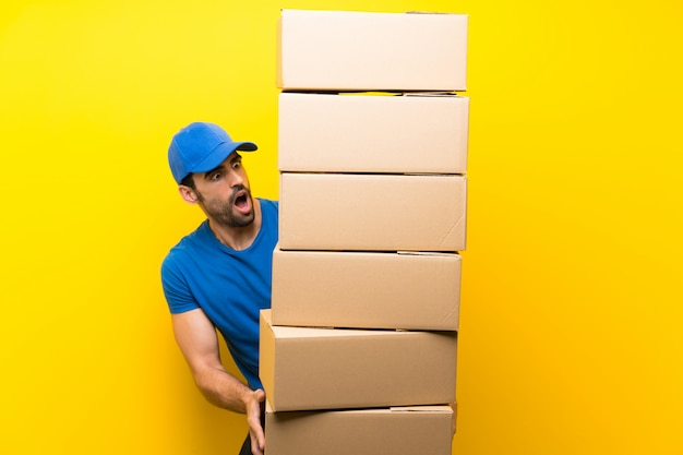 Jovem entregador sobre parede amarela isolada