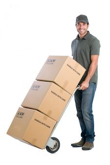 Jovem entregador sorridente movendo caixas com dolly, isolado no fundo branco