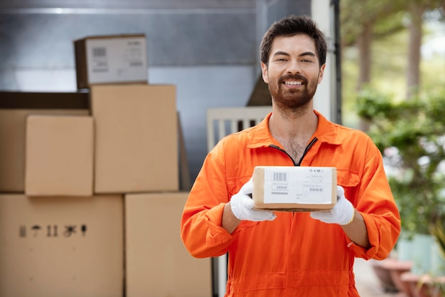 Jovem entregador sorridente preparando pacotes para entrega