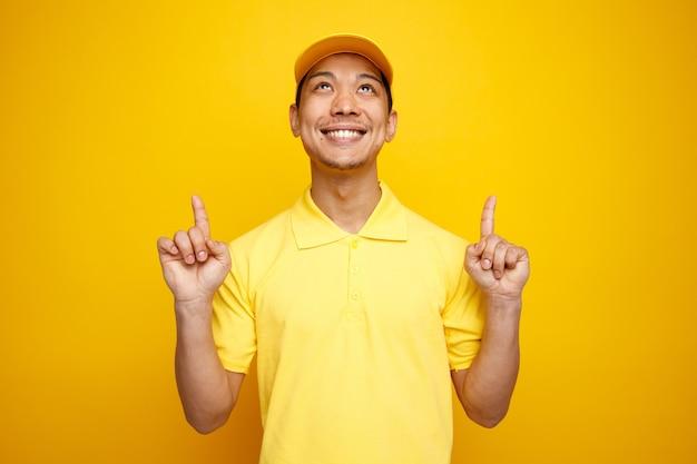 Jovem entregador sorridente usando boné e uniforme, olhando e apontando para cima