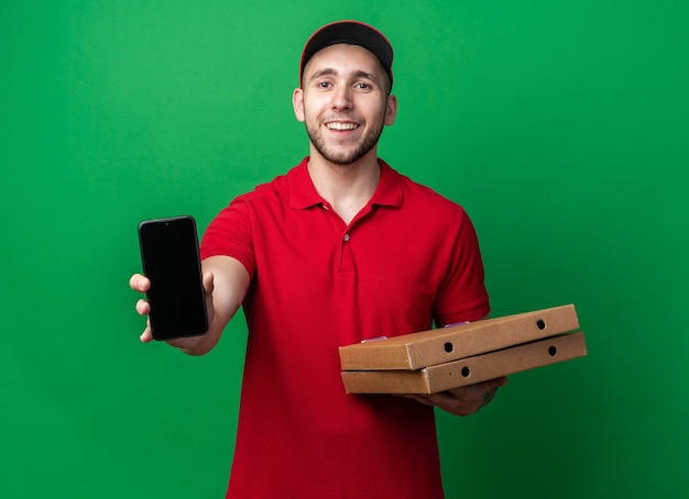 Jovem entregador sorridente, usando uniforme com tampa, segurando caixas de pizza com telefone