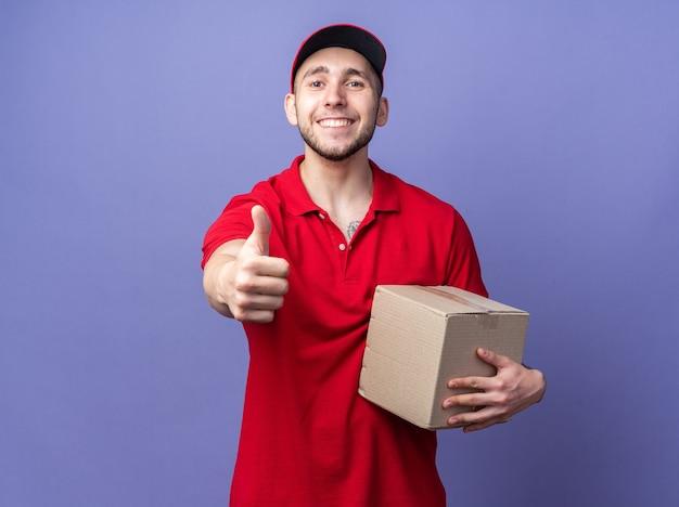 Jovem entregador sorridente usando uniforme com tampa segurando uma caixa aparecendo com o polegar