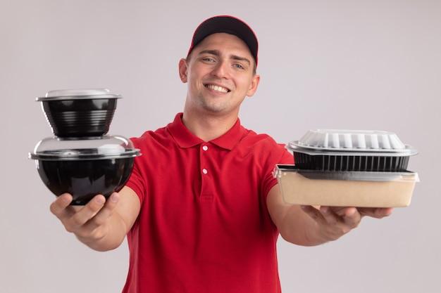 Jovem entregador sorridente, vestindo uniforme com tampa, segurando recipientes de comida para a câmera, isolada na parede branca