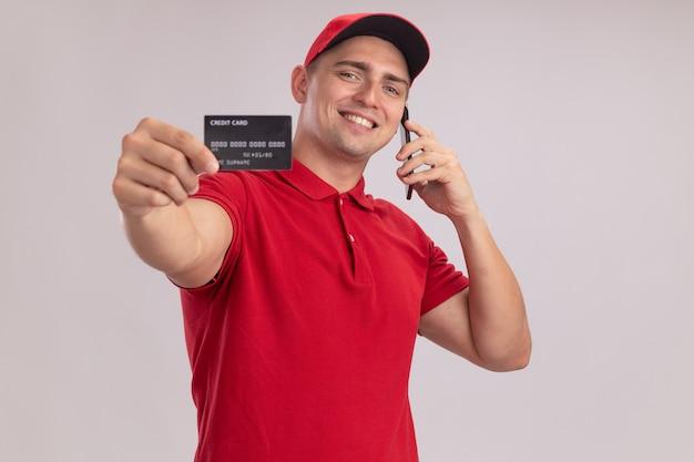 Jovem entregador sorridente, vestindo uniforme com tampa segurando um cartão de crédito falando no telefone isolado na parede branca