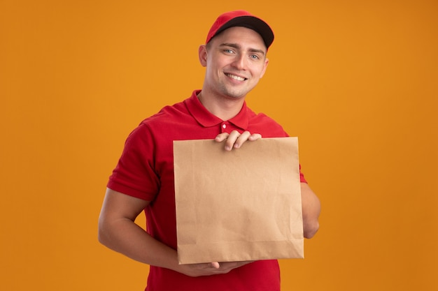 Jovem entregador sorridente, vestindo uniforme com tampa segurando um pacote de comida de papel isolado na parede laranja