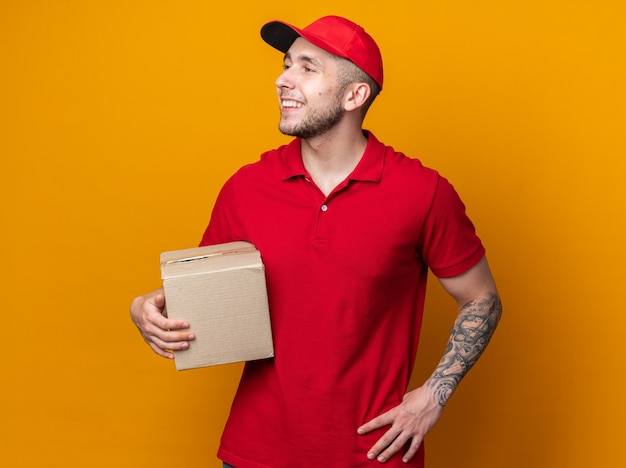 Jovem entregador sorrindo olhando para o lado, vestindo uniforme com boné segurando a caixa e colocando a mão no quadril