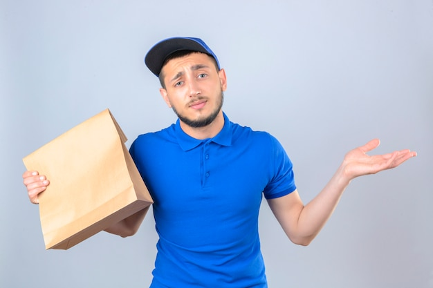Jovem entregador vestindo camisa pólo azul e boné em pé com um pacote de papel com comida para viagem confusa com as mãos levantadas sobre um fundo branco isolado