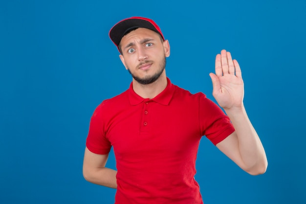 Jovem entregador vestindo camisa pólo vermelha e boné em pé com a mão aberta, fazendo sinal de pare com gesto de defesa de expressão sério e confiante sobre fundo azul isolado