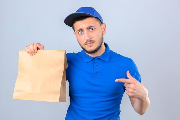 Jovem entregador vestindo uma camisa pólo azul e boné segurando um pacote de papel com comida para viagem apontando para este pacote com o dedo sobre um fundo branco isolado