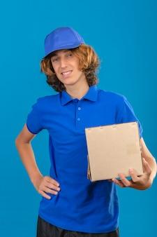 Jovem entregador vestindo uma camisa pólo azul e boné segurando uma caixa de papelão sorrindo amigável em pé sobre fundo azul