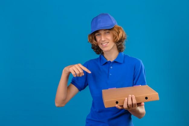 Jovem entregador vestindo uma camisa pólo azul e boné segurando uma caixa de pizza apontando o dedo indicador para a caixa enquanto olha para a câmera com um grande sorriso no rosto, de pé sobre um fundo azul isolado