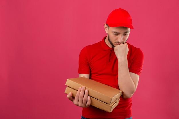 Jovem entregador vestindo uma camisa pólo vermelha e boné em pé com uma pilha de caixas de pizza, parecendo triste e infeliz olhando de lado com a mão pressionada contra o queixo sobre um fundo rosa isolado