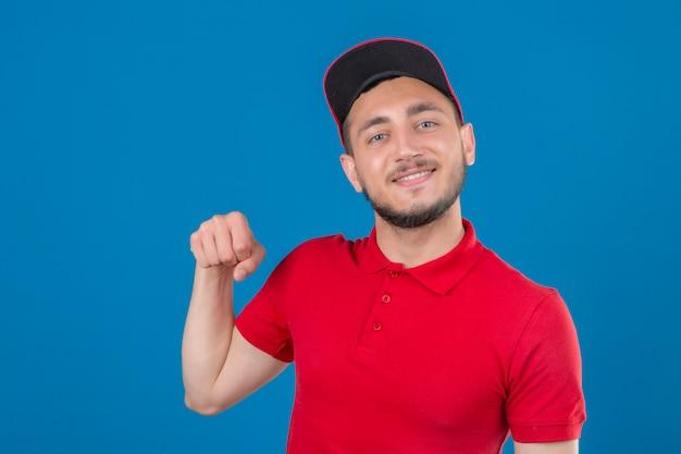 Jovem entregador vestindo uma camisa pólo vermelha e boné olhando para a câmera sorrindo amigável gesticulando com o punho como se cumprimentando, aprovando ou em sinal de respeito sobre um fundo azul isolado