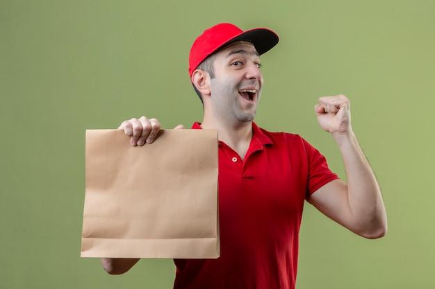 Jovem entregador vestindo uniforme vermelho segurando um pacote de papel levantando o punho e comemorando a vitória com uma cara feliz sobre um fundo verde isolado