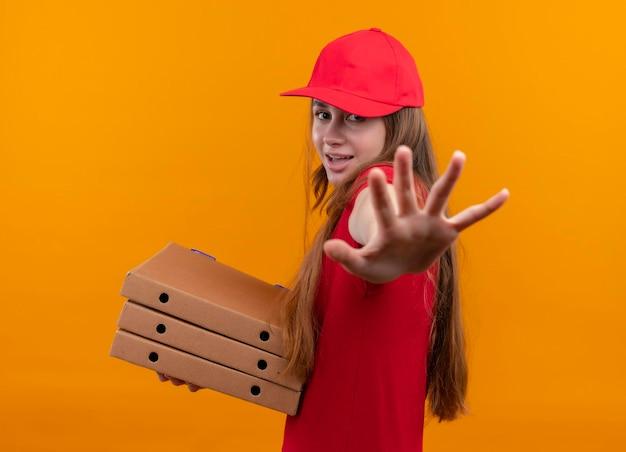 Jovem entregadora alegre de uniforme vermelho segurando pacotes, estendendo a mão em pé em vista de perfil no espaço laranja isolado