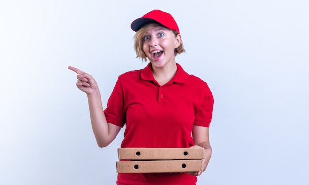 Jovem entregadora animada, usando uniforme e boné, segurando caixas de pizza e pontos ao lado, isolados na parede branca com espaço de cópia