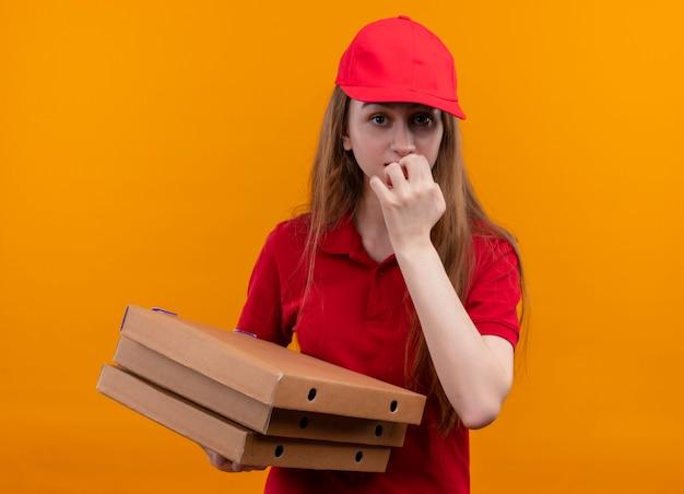 Jovem entregadora ansiosa de uniforme vermelho segurando pacotes com a mão nos lábios em um espaço laranja isolado