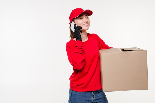 Jovem entregadora asiática usando smartphone móvel, falando com o cliente, verificando o endereço de entrega