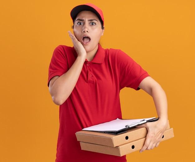 Jovem entregadora assustada vestindo uniforme e boné segurando caixas de pizza e prancheta colocando a mão na bochecha isolada na parede laranja