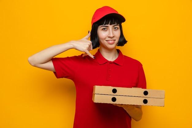 Jovem entregadora caucasiana satisfeita segurando caixas de pizza e gesticulando para me ligar