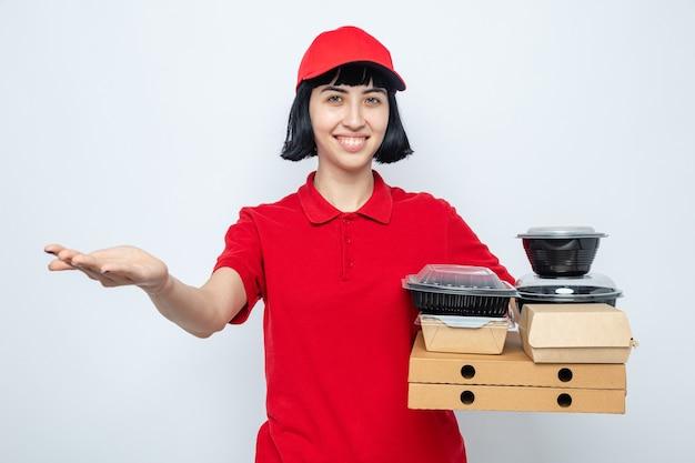 Jovem entregadora caucasiana sorridente segurando recipientes de comida e embalagens em caixas de pizza, mantendo a mão aberta