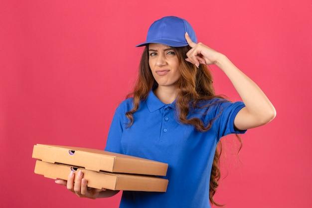 Jovem entregadora com cabelo encaracolado, usando uma camisa pólo azul e boné, mostrando um gesto de decepção com o indicador sobre um fundo rosa isolado