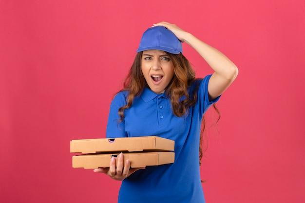 Jovem entregadora com cabelo encaracolado, vestindo uma camisa pólo azul e boné em pé com caixas de pizza chocadas com a mão na cabeça por engano, lembre-se do erro, esqueci o conceito de memória ruim sobre rosa isolado b